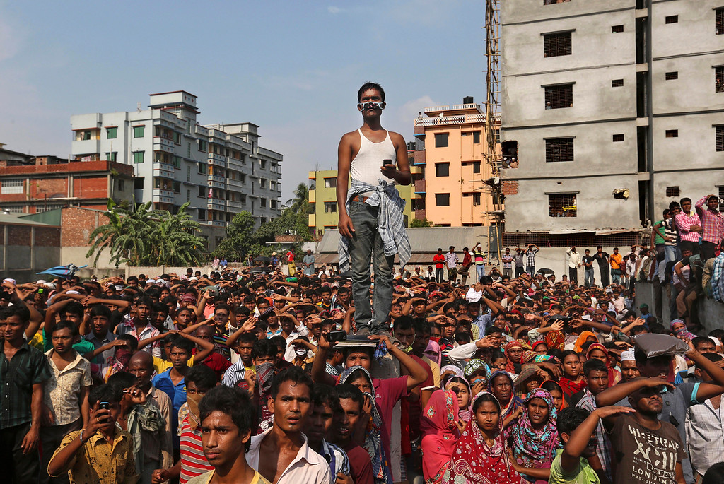 . Bangladeshis watch the rescue operations at the site of a building that collapsed Wednesday in Savar, near Dhaka, Bangladesh, Thursday, April 25, 2013.  (AP Photo/Kevin Frayer)