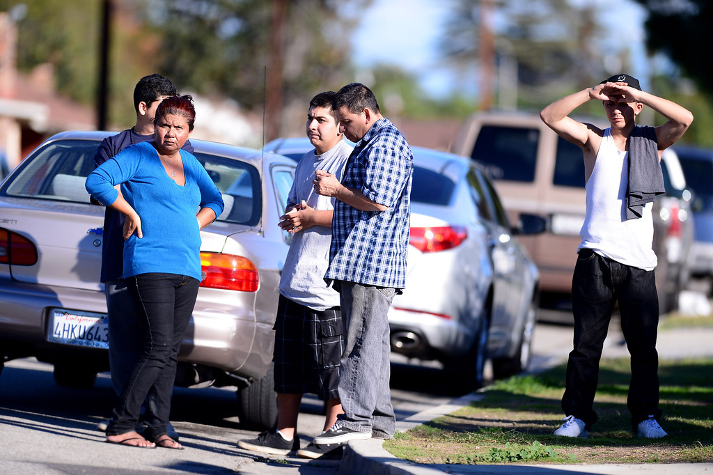 . Residents watch Pomona Police detectives investigate a shooting of a teenage girl in the 1000 block of Laurel Avenue in Pomona Saturday, November 30, 2013.  The city has been plagued by violence, with 27 homicides this year. Police are offering $10,000 rewards for information leading to conviction in any of this year\'s unsolved killings. (Photo by Sarah Reingewirtz/Pasadena Star-News)