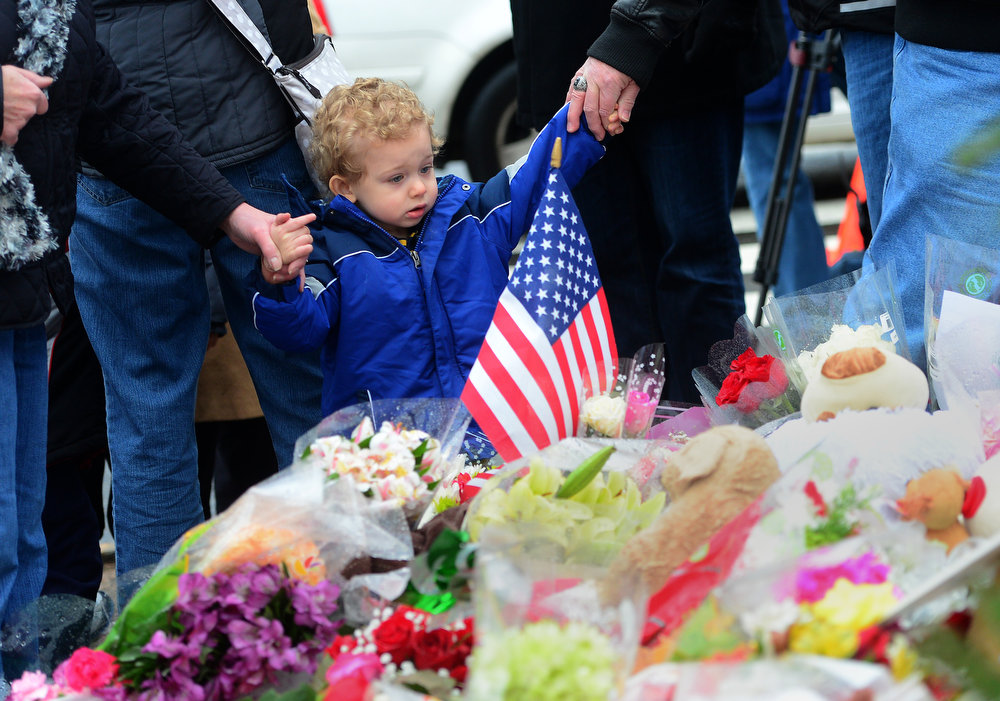 . People pay their respects at a makeshift shrine to the victims of an elementary school shooting in Newtown, Connecticut, December 17, 2012.  Funerals began Monday in the little Connecticut town of Newtown after the school massacre that took the lives of 20 small children and six staff, triggering new momentum for a change to America\'s gun culture.    AFP PHOTO/Emmanuel DUNAND/AFP/Getty Images