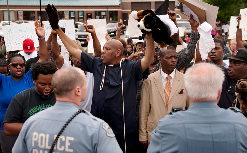 . Protestors raise their hands during an impromptu rally, Sunday, Aug. 10, 2014 to protest the shooting of Michael Brown, 18, by police in Ferguson, Mo.  Saturday, Aug. 9, 2014. Brown died following a confrontation with police, according to St. Louis County Police Chief Jon Belmar, who spoke at a news conference Sunday. (AP Photo/Sid Hastings)