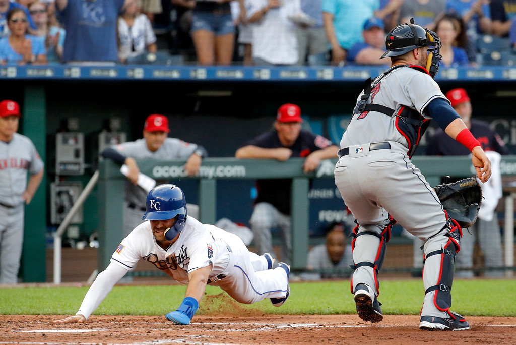. Kansas City Royals\' Whit Merrifield dives home to score on a double by Rosell Herrera during the second inning of a baseball game against the Cleveland Indians on Tuesday, July 3, 2018, in Kansas City, Mo. (AP Photo/Charlie Riedel)