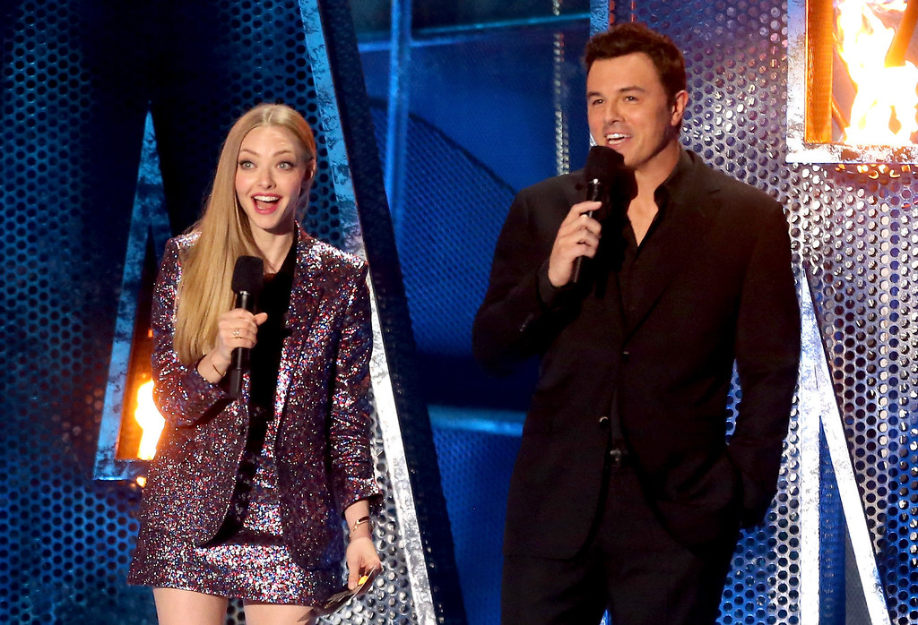 . Actors Amanda Seyfried (L) and Seth MacFarlane speak onstage at the 2014 MTV Movie Awards at Nokia Theatre L.A. Live on April 13, 2014 in Los Angeles, California.  (Photo by Frederick M. Brown/Getty Images)