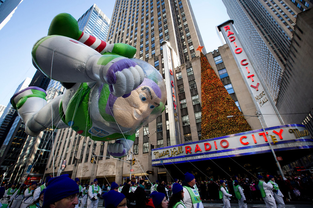 . A giant Buzz Lightyear balloon is marched down 6th Avenue during the 87th Annual Macy\'s Thanksgiving Day Parade, Thursday, Nov. 28, 2013, in New York. After fears the balloons could be grounded if sustained winds exceeded 23 mph, Snoopy, Spider-Man and the rest of the iconic balloons received the all-clear from the New York Police Department to fly between Manhattan skyscrapers on Thursday. (AP Photo/John Minchillo)