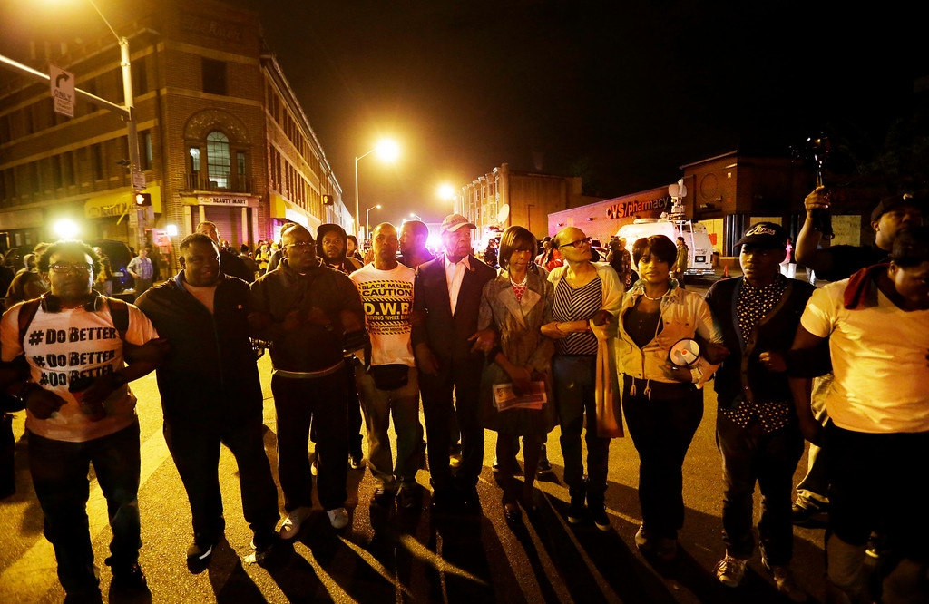 . Community leaders join arms in an effort to clear a crowd from an intersection ahead of a 10 p.m. curfew Thursday, April 30, 2015, in Baltimore. The curfew was imposed after unrest in the city over the death of Freddie Gray while in police custody. (AP Photo/David Goldman)