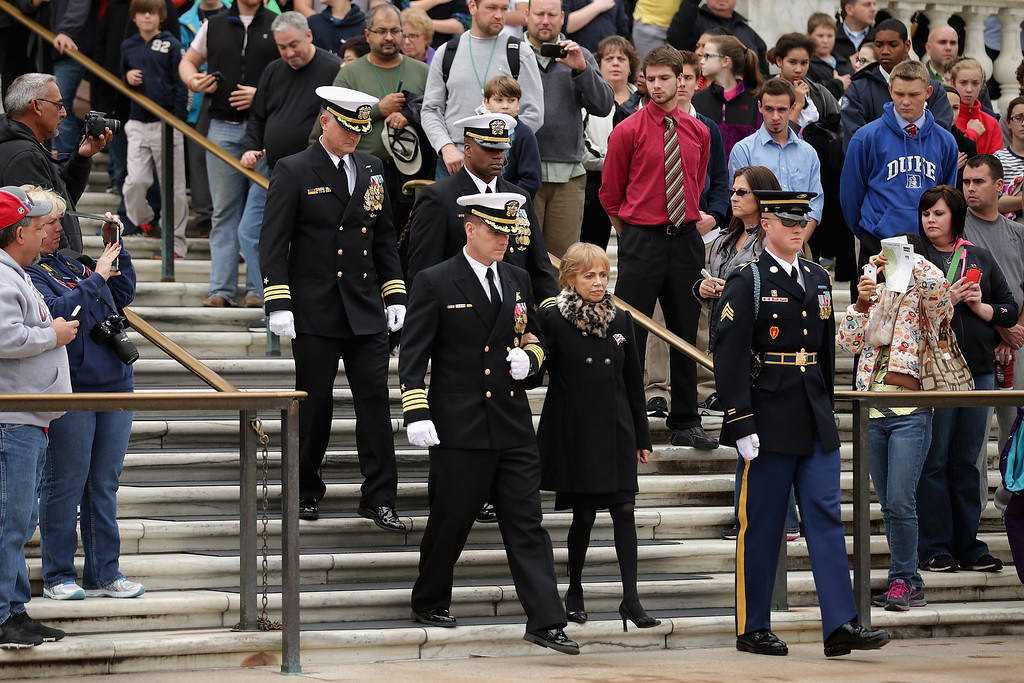 . Accompanied by members of the U.S. Navy SEALs, Carmella LaSpada (C), White House Special Projects Aide to President John F. Kennedy, participates in a wreath laying ceremony at the Tomb of the Unknowns in honor of Kennedy at Arlington National Cemetery November 22, 2013 in Arlington, Virginia. Remembrance ceremonies were held arcoss the United States today, the 50th anniversary of the assisination of President Kennedy. President Kennedy established the Navy SEALs in 1962 as a small, elite maritime military force to conduct unconventional warfare. (Photo by Chip Somodevilla/Getty Images)