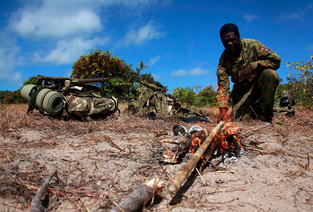 . Lance-corporal Danny Daniels, an indigenous soldier from Australia\'s North West Mobile Force (NORFORCE) unit, uses fire to remove bark from a \'spear tree\' during a surveillance and reconnaissance patrol around Astell Island, part of the English Company Islands, located inside Arnhem Land in the Northern Territory July 17, 2013. NORFORCE is a surveillance unit that employs ancient Aboriginal skills to help in the seemingly impossible task of patrolling the country\'s vast northwest coast. NORFORCE\'s area of operations is about 1.8 million square km (700,000 square miles), covering the Northern Territory and the north of Western Australia. Aboriginal reservists make up a large proportion of the 600-strong unit, and bring to bear their knowledge of the land and the food it can provide. Fish, shellfish, turtle eggs and even insects supplement rations during the patrol, which is on the lookout for illegal foreign fishing vessels and drug smugglers, as well as people smugglers from neighboring Indonesia. Picture taken July 17, 2013. REUTERS/David Gray