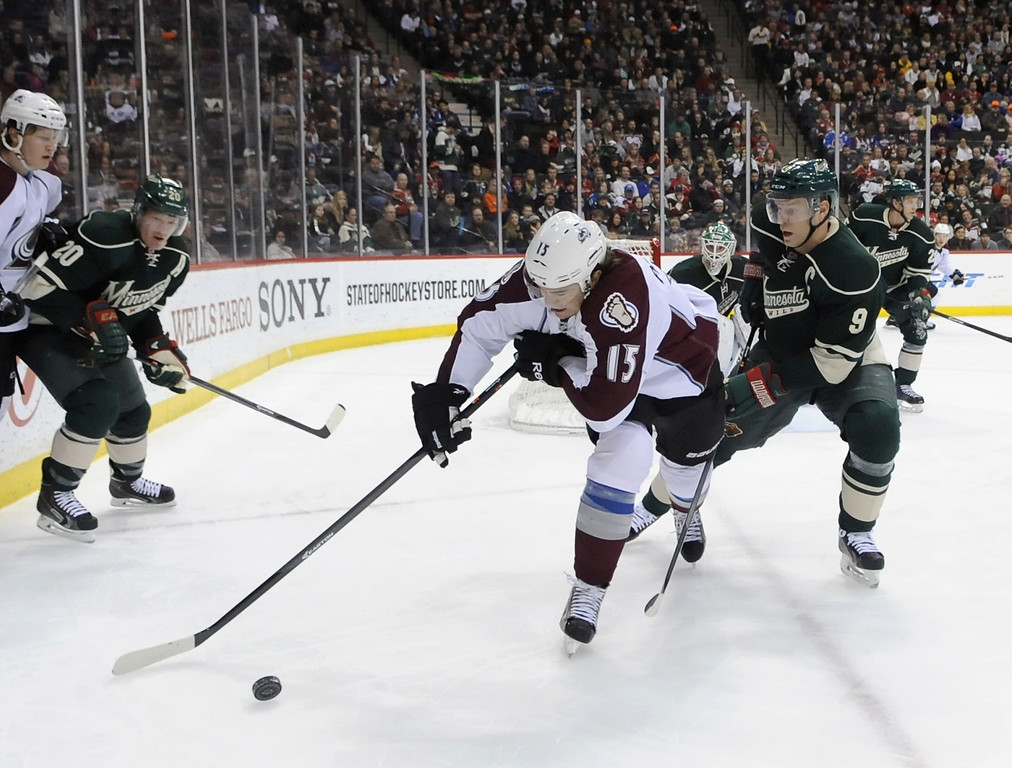 . P.A. Parenteau #15 of the Colorado Avalanche controls the puck against Mikko Koivu #9 of the Minnesota Wild during the first period of the game on November 29, 2013 at Xcel Energy Center in St Paul, Minnesota. (Photo by Hannah Foslien/Getty Images)