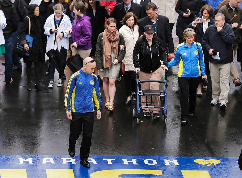 . Marathon survivor Erika Brannock, a teacher from Maryland, uses a walker as she prepares to cross the finish line following a tribute in honor of the one year anniversary of the Boston Marathon bombings, Tuesday, April 15, 2014 in Boston. (AP Photo/Charles Krupa)