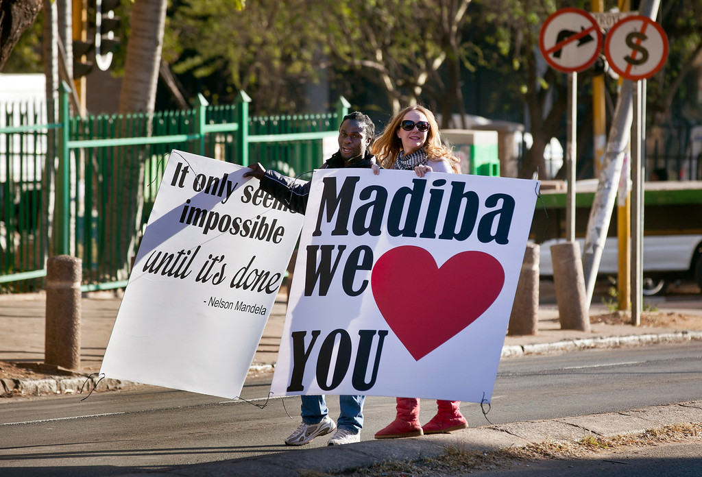 . Two wellwishers arrive carrying placards in support of former South African President Nelson Mandela, whose clan name is Madiba, outside the entrance to the Mediclinic Heart Hospital where he is being treated in Pretoria, South Africa Tuesday, June 25, 2013. South Africa\'s president Jacob Zuma on Tuesday urged his compatriots to show their appreciation for Nelson Mandela, who is in critical condition in a hospital, by marking his 95th birthday next month with acts of goodness that honor the legacy of the anti-apartheid leader. (AP Photo/Ben Curtis)