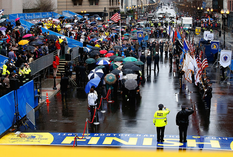 . (L-R) Former Boston mayor Thomas Menino, mayor Marty Walsh, U.S. Vice President Joe Biden, Governor Deval Patrick, and Tom Grilk, Executive Director, Boston Athletic Association stand together with members of the victims families during the flag raising ceremony commemorating the one-year anniversary of the Boston Marathon bombings on Boylston Street near the finish line on April 15, 2014 in Boston, Massachusetts.  Last year, two pressure cooker bombs killed three and injured an estimated 264 others during the Boston marathon, on April 15, 2013.  (Photo by Jared Wickerham/Getty Images)