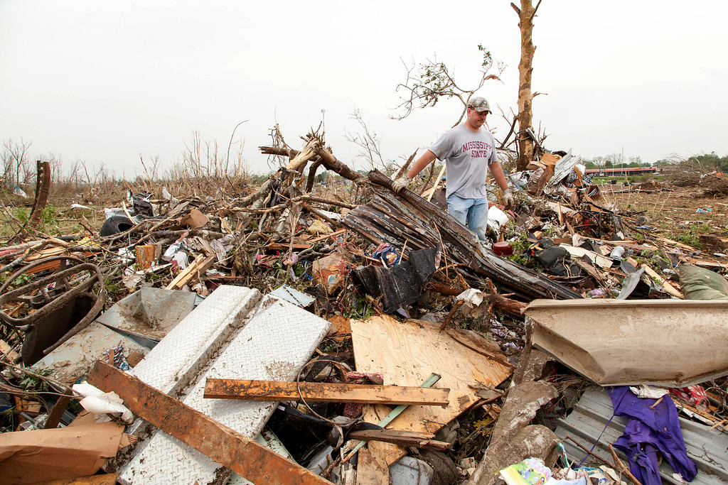 . Dino McLaughlin crawls over a pile of debris which is all that\'s left of his friends storage unit in Vilonia, Ark., Monday, April 28, 2014 after a tornado struck the town late Sunday.  McLaughkin said his friend and his wife are building a new home and had many of their possessions in the storage building. They did not have insurance.  (AP Photo/Karen E. Segrave)