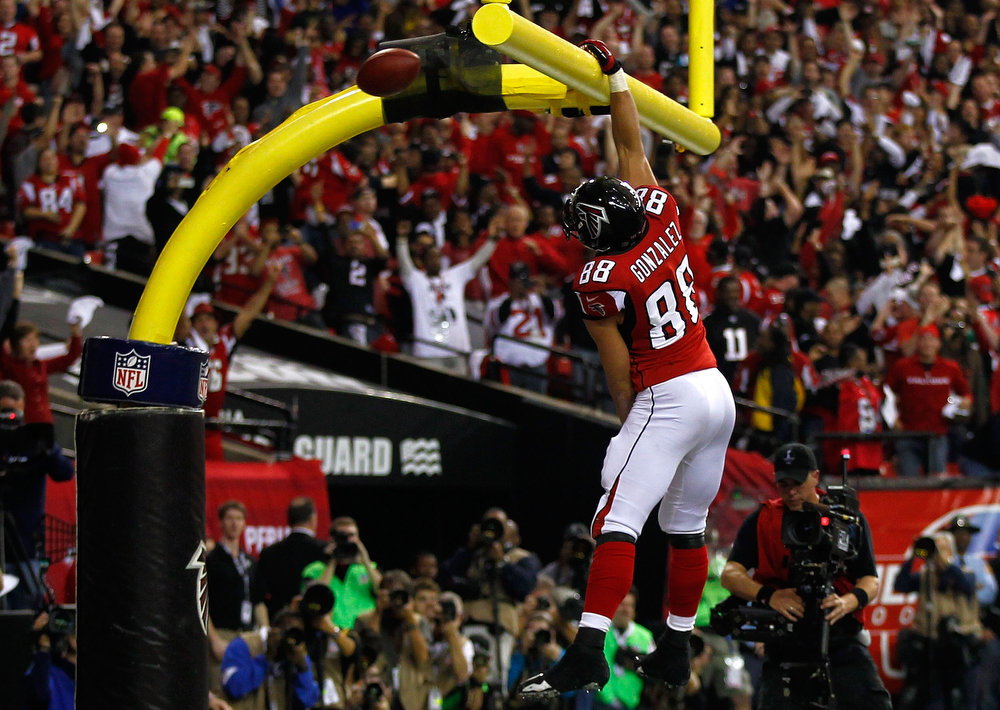 Description of . Tight end Tony Gonzalez #88 of the Atlanta Falcons dunks the ball over the goal post after catching a 10-yard touchdown in the second quarter against the San Francisco 49ers in the NFC Championship game at the Georgia Dome on January 20, 2013 in Atlanta, Georgia.  (Photo by Mike Ehrmann/Getty Images)