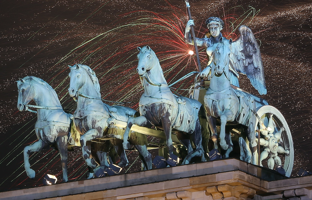 . BERLIN, GERMANY - JANUARY 01:  Fireworks explode behind the Quadriga statue on top of the Brandenburg Gate shortly after midnight on January 1, 2015 in Berlin, Germany. Tens of thousands of revelers gathered in the city center to celebrate New Year\'s Eve.  (Photo by Adam Berry/Getty Images)