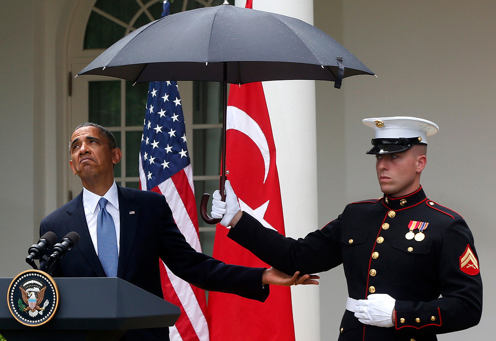 . President Barack Obama looks to see if it is still raining as a Marine holds an umbrella for him during his joint news conference with Turkish Prime Minister Recep Tayyip Erdogan, not pictured, Thursday, May 16, 2013, in the Rose Garden of the White House in Washington. (AP Photo/Charles Dharapak)