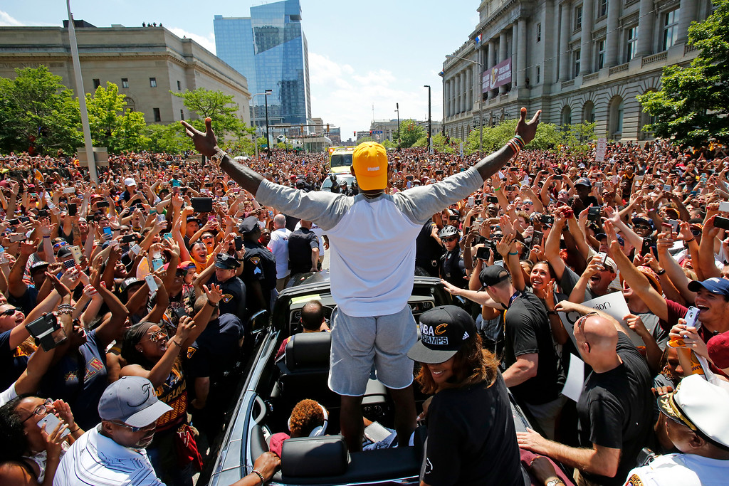 . Cleveland Cavaliers\' LeBron James, center, stands in the back of a Rolls Royce as it makes its way through the crowd lining the parade route in downtown Cleveland, Wednesday, June 22, 2016, celebrating the basketball team\'s NBA championship. The Cleveland Sports Commission says 1.3 million people went downtown to celebrate the city\'s first championship in 52 years. (AP Photo/Gene J. Puskar)