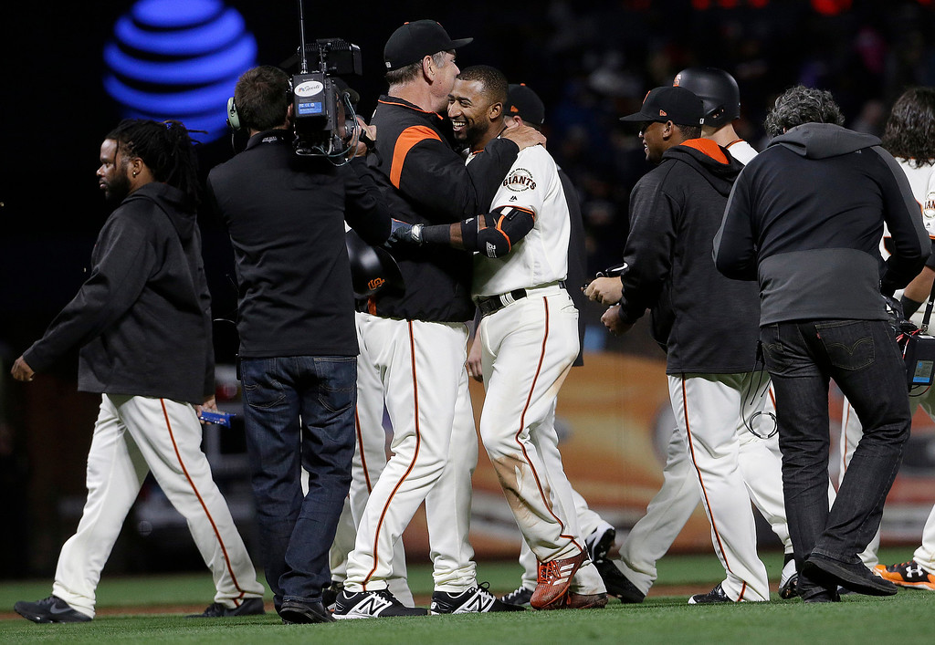 . San Francisco Giants\' Eduardo Nunez, center right, hugs manager Bruce Bochy after singling to score Kelby Tomlinson for the winning run during the tenth inning of a baseball game against the Cleveland Indians in San Francisco, Tuesday, July 18, 2017. The Giants won 2-1 in ten innings. (AP Photo/Jeff Chiu)