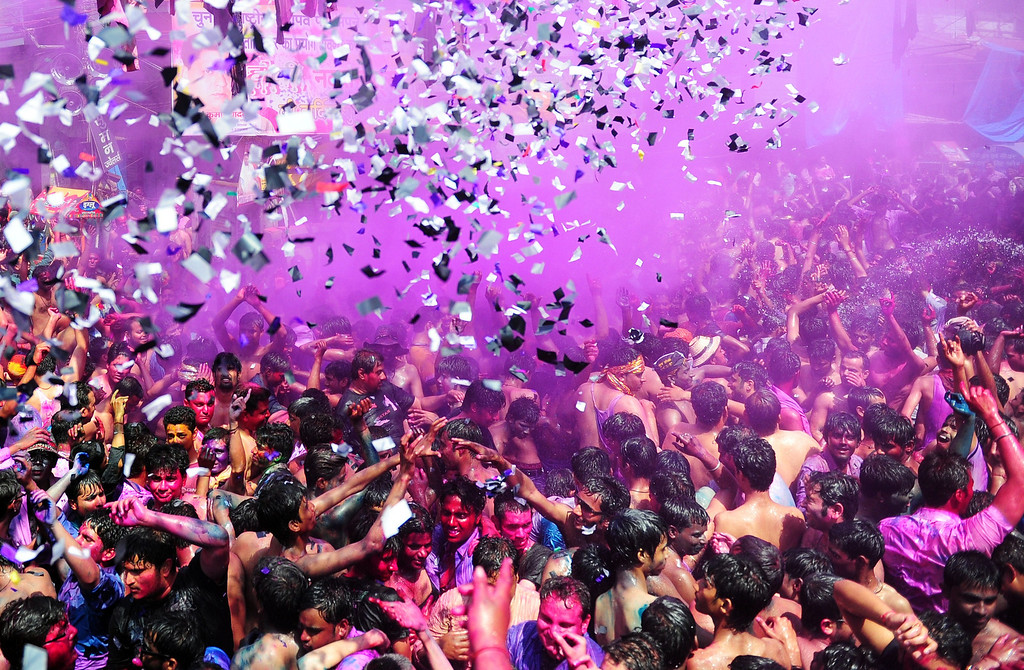. Indian revelers covered in colored powder dance during Holi festival celebrations in Allahabad on March 17, 2014. Holi, the popular Hindu spring festival of colors is observed in India at the end of the winter season on the last full moon of the lunar month. AFP PHOTO/SANJAY KANOJIASanjay Kanojia/AFP/Getty Images
