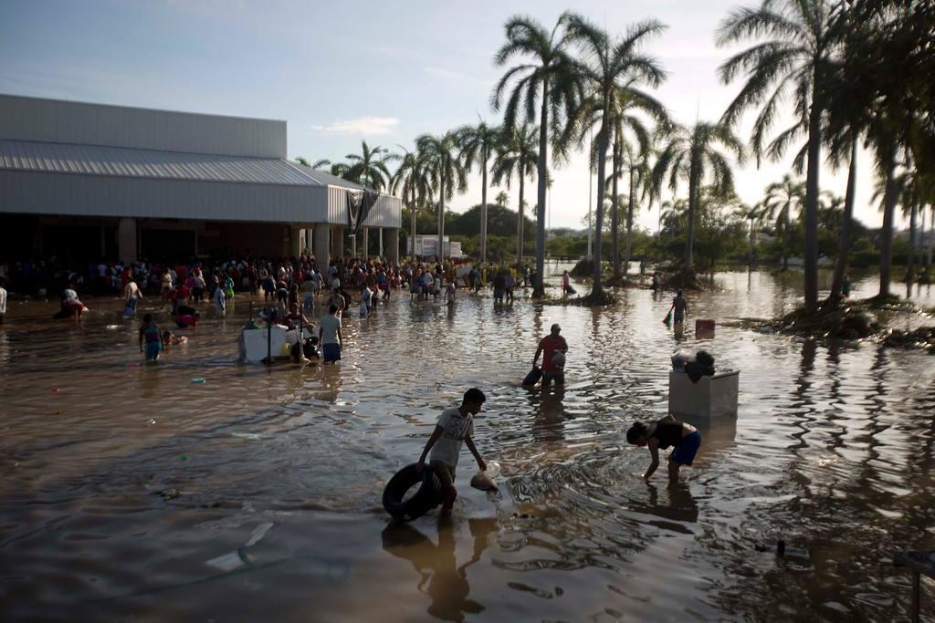 . People wade through waist-high water in a store\'s parking, looking for valuables, south of Acapulco, in Punta Diamante, Mexico, Wednesday, Sept. 18, 2013. Mexico was hit by the one-two punch of twin storms over the weekend, and the storm that soaked Acapulco on Sunday - Manuel -re-formed into a tropical storm Wednesday, threatening to bring more flooding to the country\'s northern coast. With roads blocked by landslides, rockslides, floods and collapsed bridges, Acapulco was cut off from road transport. (AP Photo/Eduardo Verdugo)