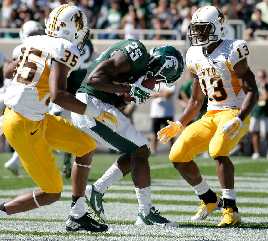. Michigan State\'s Keith Mumphery (25) catches a pass for a touchdown between Wyoming\'s Robert Priester (35) and Darrenn White (13) during the second quarter of an NCAA college football game, Saturday, Sept. 27, 2014, in East Lansing, Mich. Michigan State won 56-14. (AP Photo/Al Goldis)