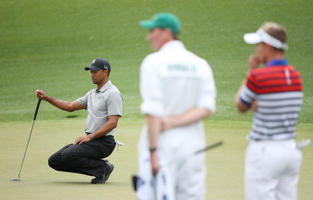 . Tiger Woods of the United States lines up a putt on the the eighth green as Luke Donald of England looks on during the first round of the 2013 Masters Tournament at Augusta National Golf Club on April 11, 2013 in Augusta, Georgia.  (Photo by Andrew Redington/Getty Images)
