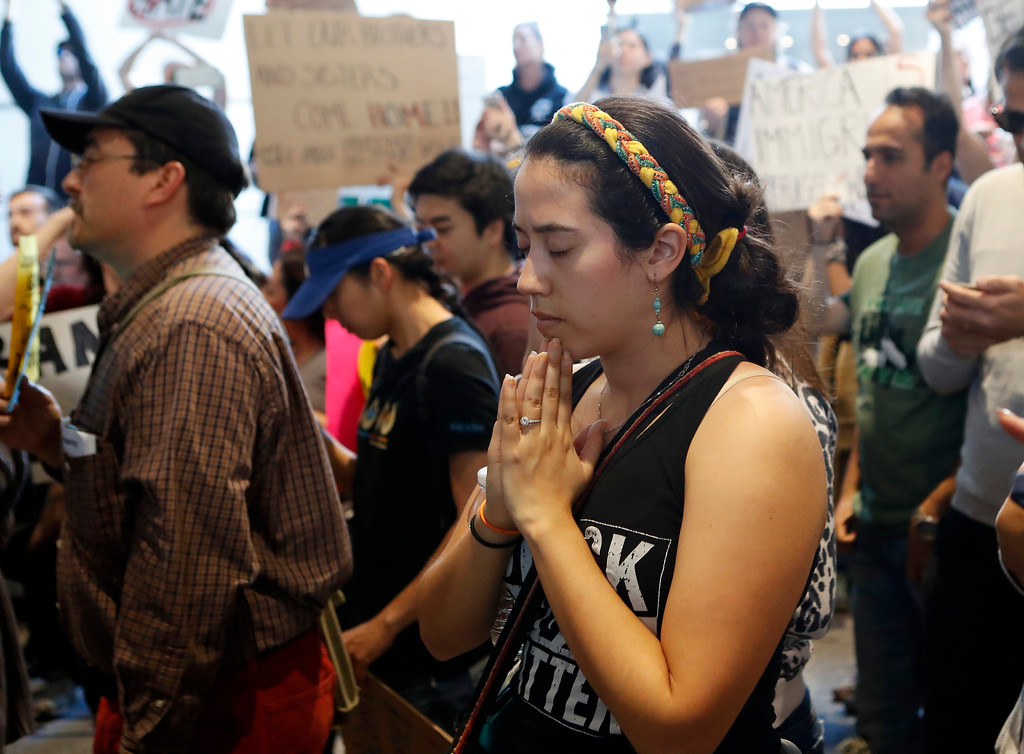 . A demonstrator prays as protests against President Donald Trump\'s executive order banning travel from seven Muslim-majority countries continue at Los Angeles International Airport Sunday, Jan. 29, 2017. (AP Photo/Ryan Kang)