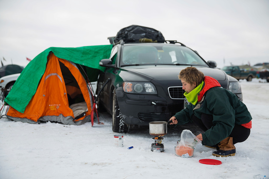 . Morgan Heckerd, of Maine, cooks lentils and tomatoes on a portable stove next to her tent at the Oceti Sakowin camp where people have gathered to protest the Dakota Access oil pipeline in Cannon Ball, N.D., Friday, Dec. 2, 2016. (AP Photo/David Goldman)