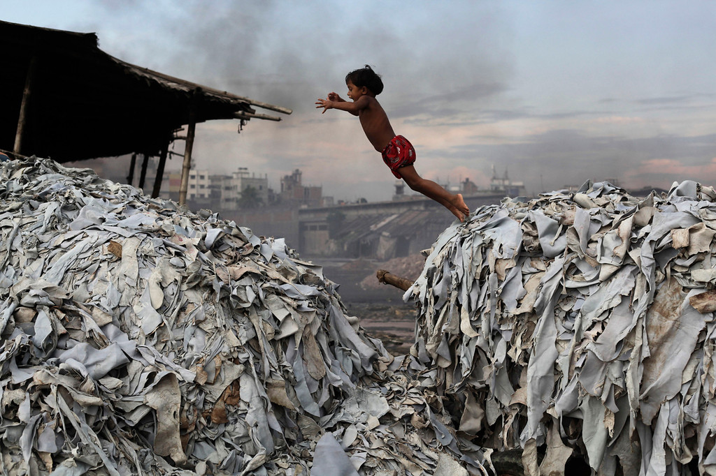 . A child jumps on the waste products that are used to make poultry feed as she plays in a tannery at Hazaribagh in Dhaka October 9, 2012. Luxury leather goods sold across the world are produced in a slum area of Bangladesh\'s capital where workers, including children, are exposed to hazardous chemicals and often injured in horrific accidents, according to a study released on Tuesday. None of the tanneries packed cheek by jowl into Dhaka\'s Hazaribagh neighborhood treat their waste water, which contains animal flesh, sulphuric acid, chromium and lead, leaving it to spew into open gutters and eventually the city\'s main river. REUTERS/Andrew Biraj