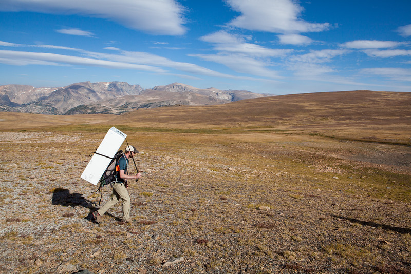 A member of the United States Geological Survey carries a freezer backpack to transport cores of ice and frozen artifacts.
