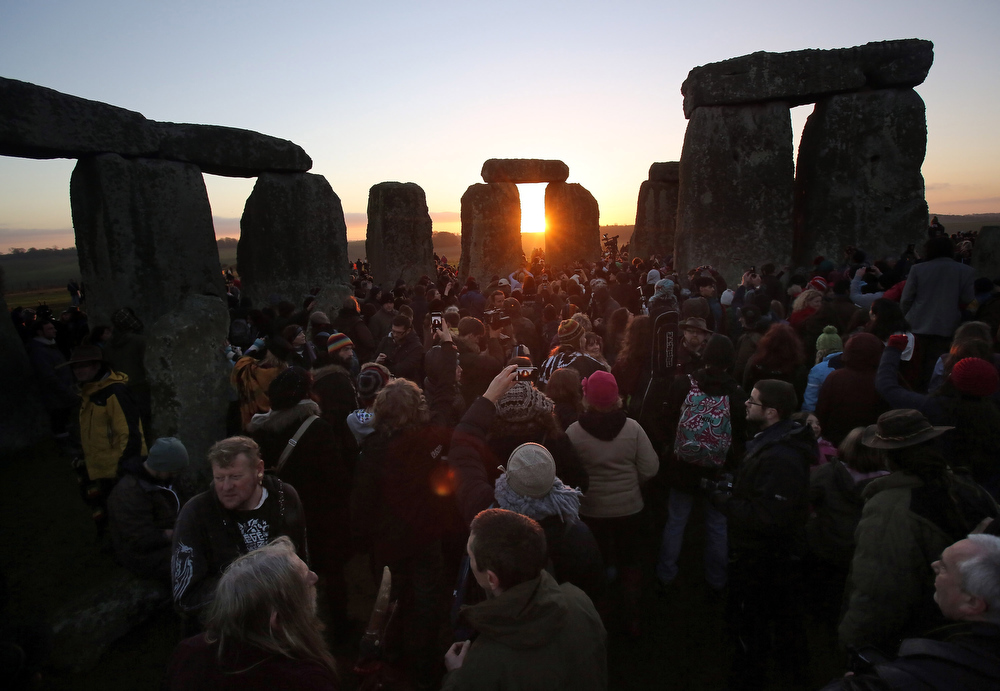 Description of . People gather to watch the sunrise as druids, pagans and revellers celebrate the winter solstice at Stonehenge on December 21, 2012 in Wiltshire, England. Predictions that the world will end today as it marks the end of a 5,125-year-long cycle in the ancient Maya calendar, encouraged a larger than normal crowd to gather at the famous historic stone circle to celebrate the sunrise closest to the Winter Solstice, the shortest day of the year.  (Photo by Matt Cardy/Getty Images)