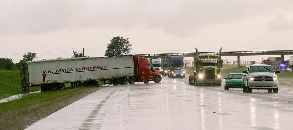 . Vehicles slowly pass by a semi tractor-trailer, which was blown off the highway by a tornado, in the Eastbound lane of Interstate-40 just east of El Reno, Oklahoma May 31, 2013. Violent thunderstorms spawned tornadoes that menaced Oklahoma City and its already hard-hit suburb of Moore on Friday, killing a mother and her baby, and officials worried that drivers stuck on freeways could be trapped in the path of dangerous twisters. One twister touched down on Interstate 40 and was headed toward Oklahoma City.  REUTERS/Bill Waugh