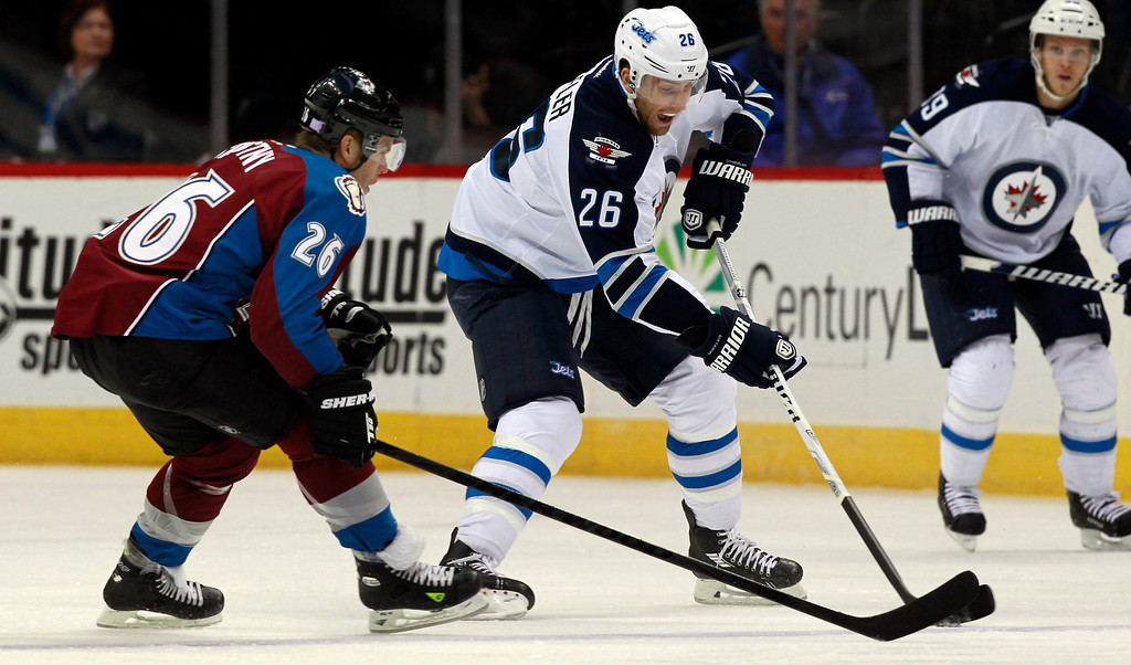 . Winnipeg Jets right wing Blake Wheeler (26) picks up loose puck as Colorado Avalanche center Paul Stastny covers in the first period of an NHL hockey game in Denver on Sunday, Oct. 27, 2013. (AP Photo/David Zalubowski)