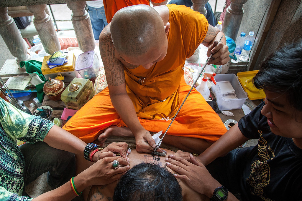 . A Thai tattoo monk master carves a tattoo on a devotee\'s back with a long needle during the celebration of the annual Tattoo festival at Wat Bang Phra on March 15, 2014 in Nakhon Pathom, Thailand.  (Photo by Omar Havana/Getty Images)