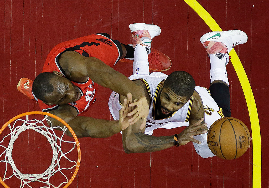 . Cleveland Cavaliers\' Kyrie Irving, right, shoots against Toronto Raptors\' Bismack Biyombo (8) during the first half of Game 2 of the NBA basketball Eastern Conference finals Thursday, May 19, 2016, in Cleveland. (AP Photo/Tony Dejak)