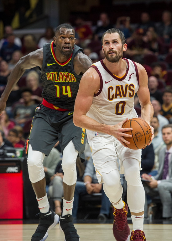 . Cleveland Cavaliers\' Kevin Love (0) drives past Atlanta Hawks\' Dewayne Dedmon (14) during the first half of an NBA pre-season basketball game in Cleveland, Wednesday, Oct. 4, 2017. (AP Photo/Phil Long)