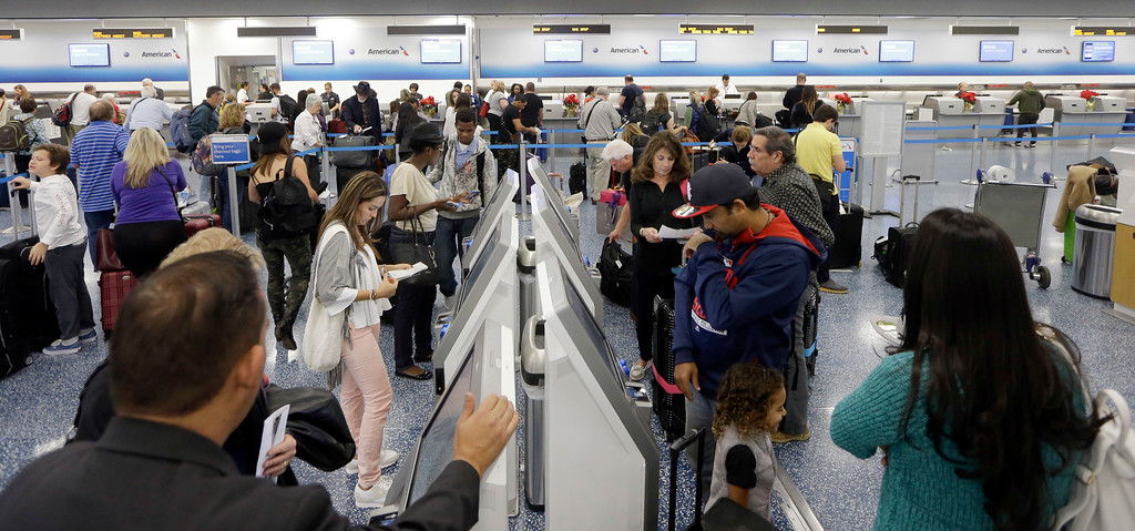 . Passengers prepare to check in at Miami International Airport, Wednesday, Nov. 23, 2016, in Miami. Almost 49 million people are expected to travel 50 miles or more for the holiday, the most since 2007, according to AAA. (AP Photo/Alan Diaz)