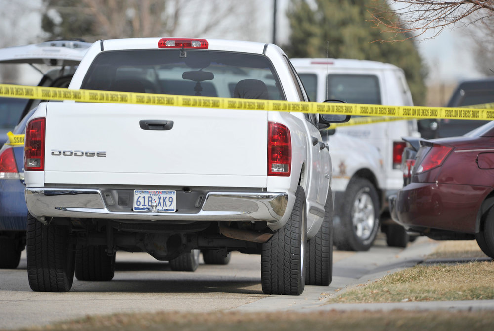 . A white Dodge pickup truck is seen running behind police tape in front of  the home where Weld County Sheriffs deputies are investigating, Tuesday, Dec. 18, 2012, in Longmont. (Matthew Jonas/Times-Call)