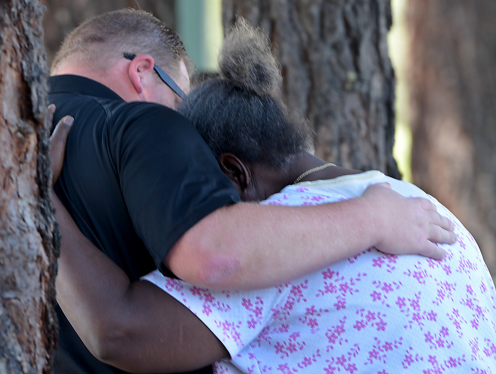 . Cynthia Johnson, the mother of a shooting victim, is comforted by David McCarthy, a San Bernardino county sheriff\'s deputy coroner, as her son\'s body is removed. San Bernardino police are investigating a shooting that left three man dead. The three were killed following a shooting early Friday, in the 1900 block of South Diners Court, police near Hospitality Lane in San Bernardino (Photo by Rick Sforza/The Sun)