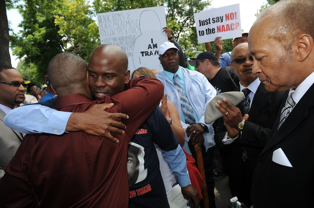 """. Jeff Fard, second from left, gets a hug from a community member as the rally gets under way in City Park in Denver, CO on July 14, 2013.  Members of the African American community turned out for a rally  to show their disappointment in the acquittal of George Zimmerman in the murder trail of Trayvon Martin on July 14, 2013.  Zimmerman is the Florida man who shot and killed Trayvon Martin. \""""We will not erase the conversation of race,\"""" said Jeff Fard, founder of Brother Jeff\'s Cultural Center in the Five Points neighborhood. \""""Don\'t be afraid to say if Trayvon Martin was a white man he would be alive today.\""""  Photo by Helen H. Richardson/The Denver Post)"""