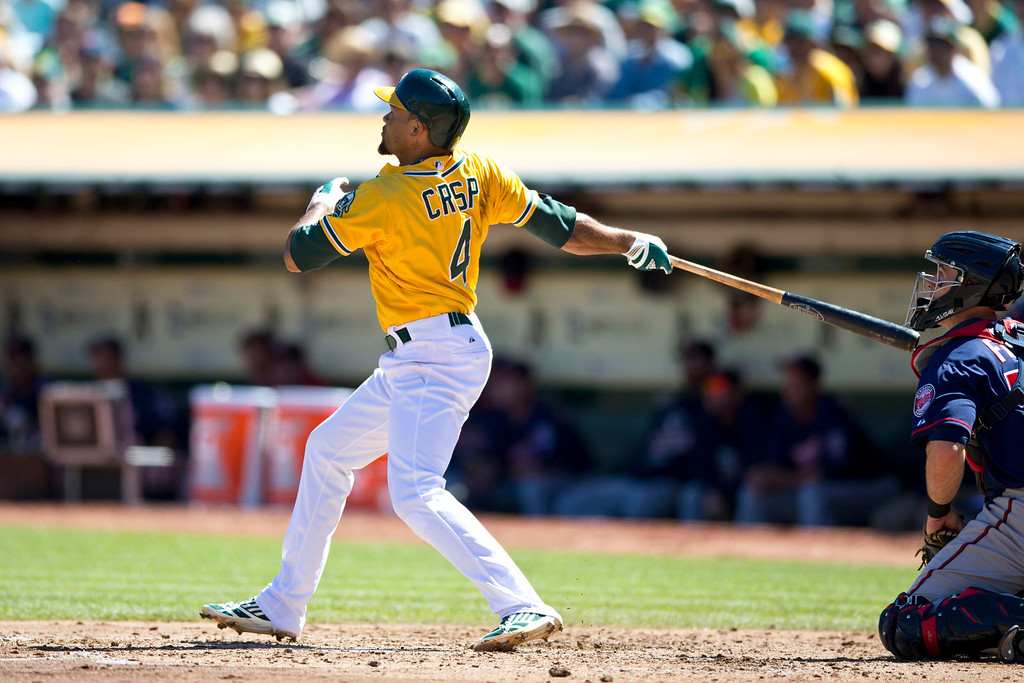 . OAKLAND, CA - SEPTEMBER 22: Coco Crisp #4 of the Oakland Athletics hits a three run home run against the Minnesota Twins during the second inning at O.co Coliseum on September 22, 2013 in Oakland, California. (Photo by Jason O. Watson/Getty Images)