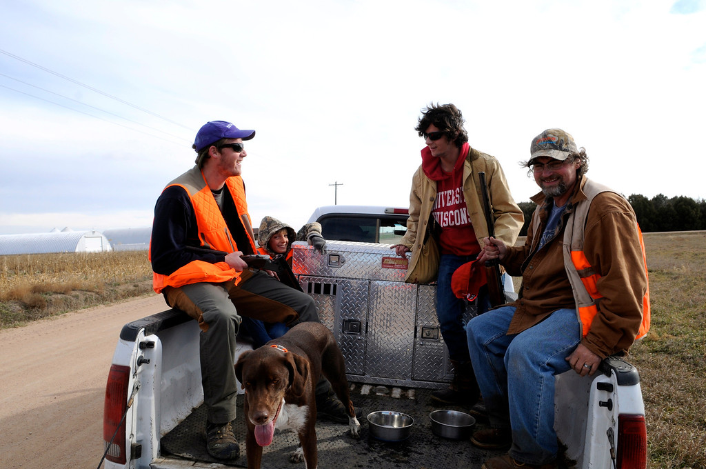 . Left to right, pheasant hunters Denton O\'Neal, Robert Gonzalez-Bringas, Miles Bragg and his father, Gary Bragg, enjoy the camaraderie of the 2013 opening weekend from dog\'s eye view in the back of a pickup near Holyoke. Scott Willoughby, The Denver Post