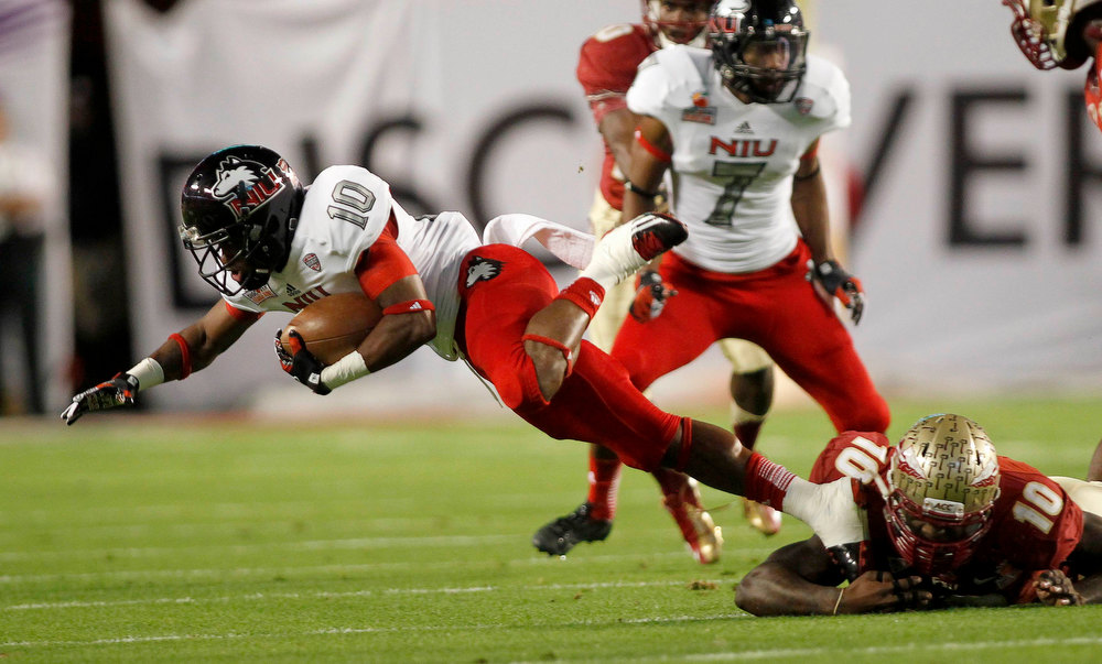 . Northern Illinois Huskies wide receiver Tommylee Lewis (L) is brought down by Florida State Seminoles linebacker Nick Moody in the first quarter during the 2013 Discover Orange Bowl NCAA football game in Miami, Florida January 1, 2013.  REUTERS/Andrew Innerarity