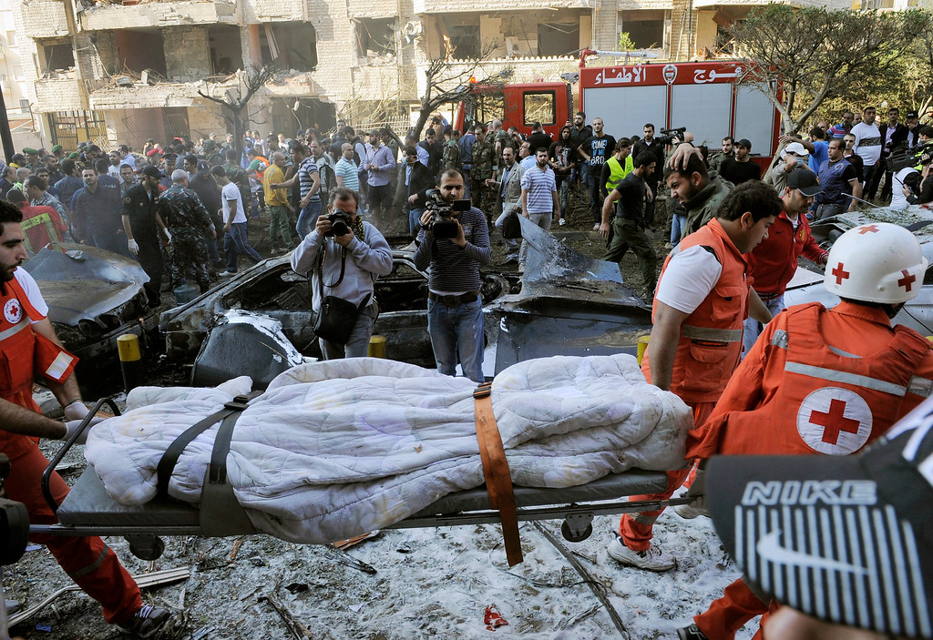 . Lebanese Red Cross members carry a blanket-wrapped body at the site of explosions near the Iranian embassy in Beirut, Lebanon, 19 November 2013. reports vary regarding fatalities but at least 15 people are believed to have been killed in south Beirut, a stronghold of the Hezbollah militant movement  EPA/WAEL HAMZEH