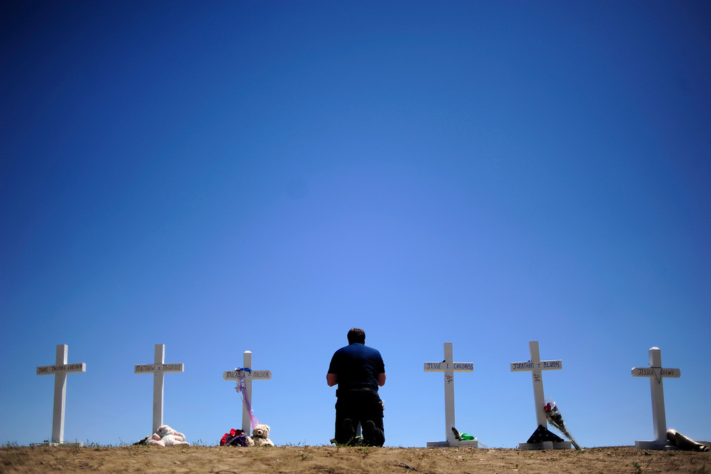 . Travis Hirko kneels at the cross of Alex Sulliven at a memorial for the victims of the Aurora Theater Shooting at the intersection of Sable Boulevard and Centerpoint Drive on Sunday, July 22, 2012. AAron Ontiveroz, The Denver Post