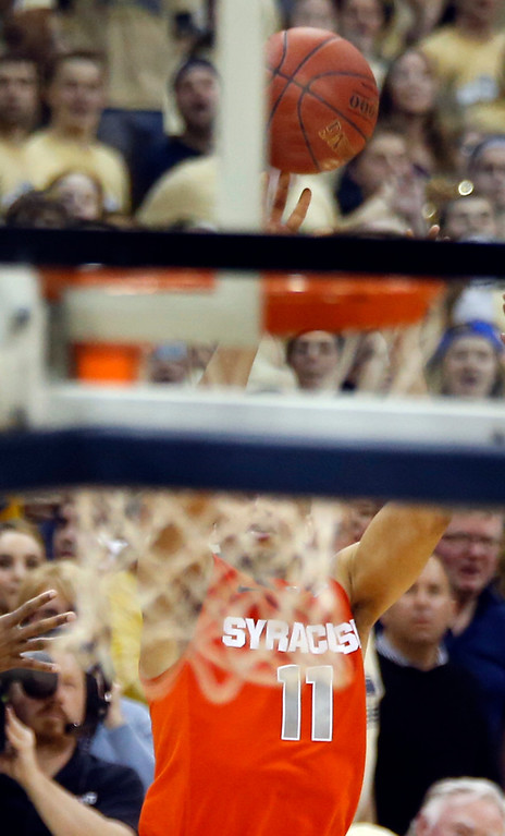 . Syracuse\'s Tyler Ennis (11) is seen through the twine of the net as he shoots a three point shot as time runs down in the second half of an NCAA college basketball game against Pittsburgh on Wednesday, Feb. 12, 2014, in Pittsburgh. The shot went in and Syracuse won 58-56 on the three point shot with less than a second left in the game. (AP Photo/Keith Srakocic)