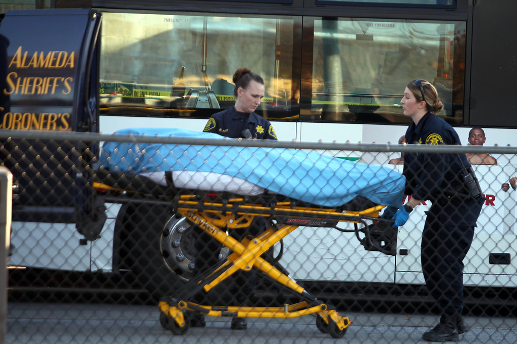 . Officers from the Alameda County Sheriff\'s Office Coroner\'s Bureau take away a body as police investigate the fatal shooting in the bus yard outside the Bay Fair BART station in San Leandro, Calif., on Saturday, Jan. 19, 2013. (Ray Chavez/Staff)