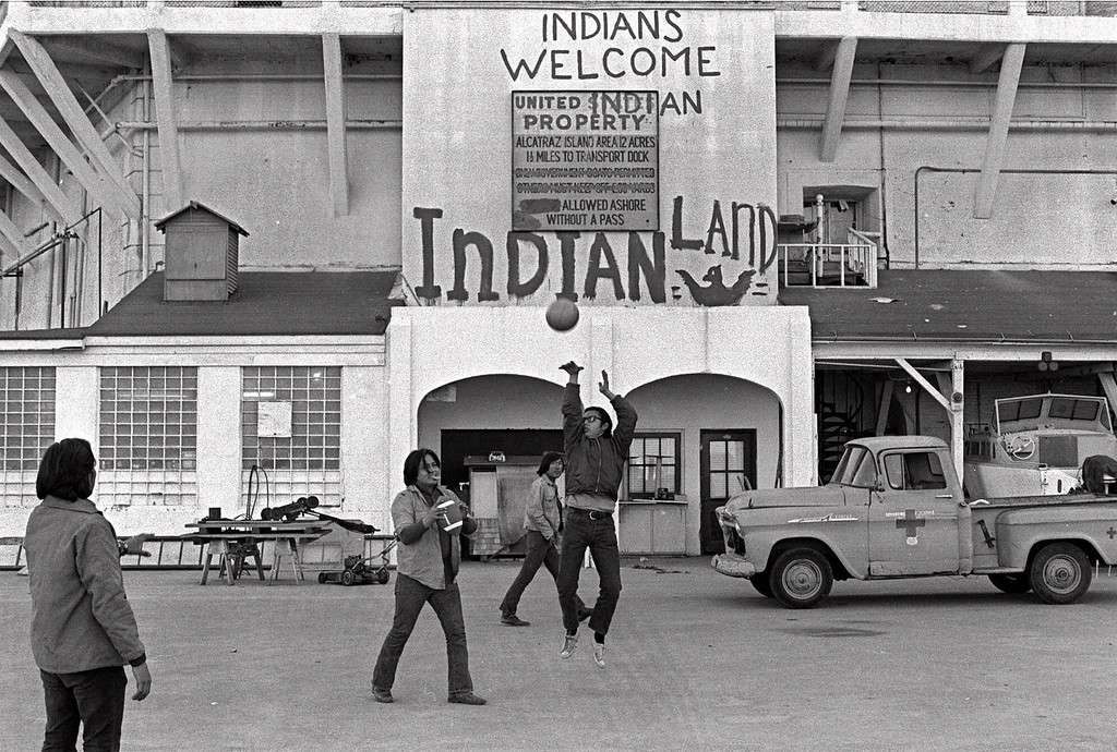 """. American Indians play ball games outside the prison wall on Alcatraz Island in San Francisco during their occupation of the island in this Nov. 26, 1969 file photo. The sign reading \""""INDIANS WELCOME,\"""" is one of the few physical reminders that 30 years ago a group of American Indians clung to the barren, bony slopes of Alcatraz for 19 months, winning the attention of the world and igniting a passion for civil rights. (AP Photo/File)"""