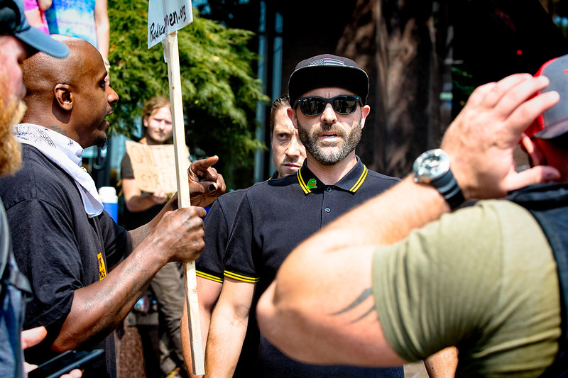 A member of the far right, wearing a Pepe The Frog pin, is confronted by a counterprotester.