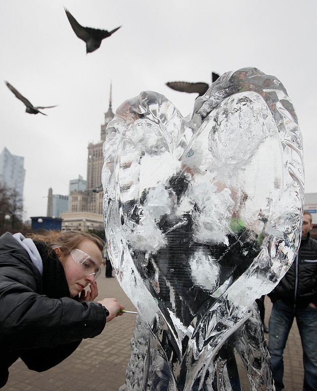 . A young woman chops into a heart-shaped piece of ice to get to a coupon for a Valentine\'s Day offering embedded in it, in Warsaw, Poland, on Friday, Feb. 14, 2014. Valentine\'s Day was introduced to Poland after the country shed communism and improved the day\'s sales of heart-shaped sweets, cakes and balloons. (AP Photo/Czarek Sokolowski)