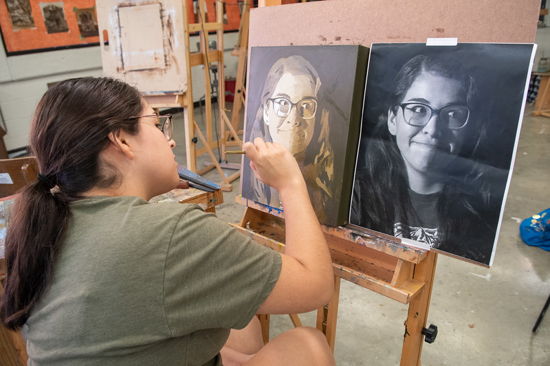 Naomi Martin works on self-portrait on canvas for her Painting II course.