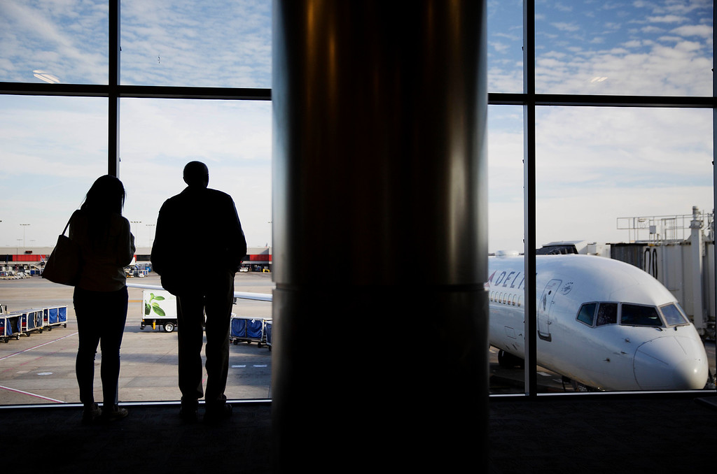 . Travelers look out a window while waiting to board a plane at Hartsfield-Jackson Atlanta International Airport ahead of the Thanksgiving holiday in Atlanta, Wednesday, Nov. 23, 2016. Almost 49 million people are expected to travel 50 miles or more for the holiday, the most since 2007, according to AAA. (AP Photo/David Goldman)